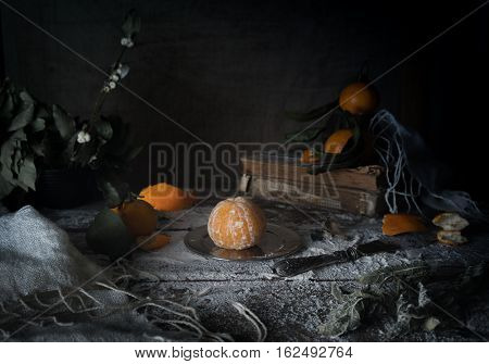 vintage. tangerines, tangerine slices, scarf and old silver knife on a wooden table.