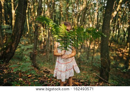 little girl standing in the forest with ferns.solitude, loneliness,