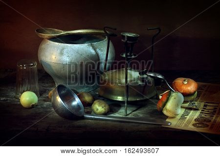 Still life with vintage items from grandma's larder. On the table are a cast-iron kettle, pot, primus, glasses. On the newspaper on a wooden table little unusual pumpkin. The photo was taken using a light brush effect it.