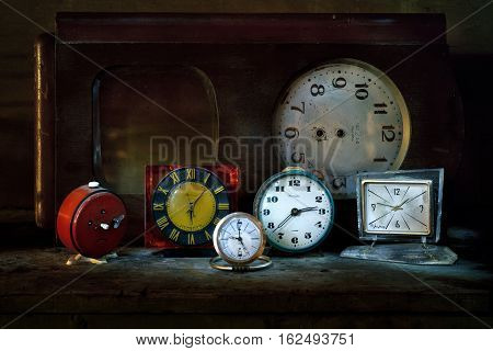 On a wooden stoel is a group of objects. Vintage rare Soviet watches, alarm clocks. The photo was taken using a light brush effect it.
