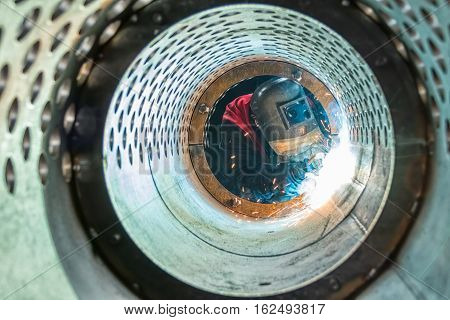 Welder welding metal pipes in tunnel made of rounded steel pipe.
