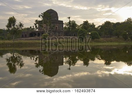 MANDU, INDIA - NOVEMBER 17, 2008: Historic building Dai ki Chhoti Bahan ka Mahal on the edge of a lake inside the hilltop fort of Mandu in Madyha Pradesh, India. Islamic style architecture, constructed from 15th