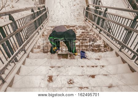 boy shoveling snow from the stairs. child cleans the stairway overpass after snowfall.view from above. the concept of selfless assistance, citizen responsibility
