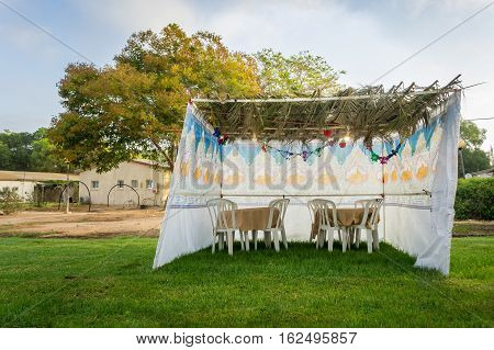 Fabric sukkah decorated with printed pattern and hebrew text of blessing: Grant peace everywhere goodness and blessing Grace lovingkindness and mercy to us and unto all Israel Your people.