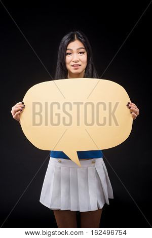 Portrait of Asian woman holding blank poster for expressing emotions or ideas isolated on black background in studio. Studio shot.