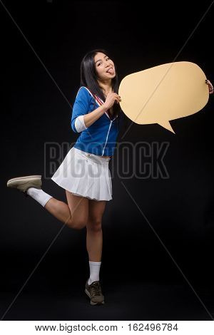 Pretty woman showing tongue and holding note for expressing emotions or ideas isolated on black background in studio. Happy Asian woman posing in full length and holding blank poster.
