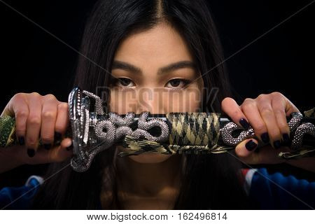 Beautiful brunette lady ready for battle isolated on black background. Asian lady holding sword in front of her in studio.