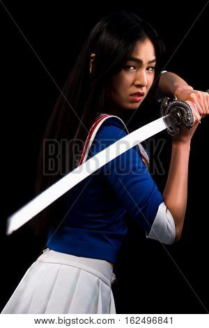 Asian lady with sword in studio. Japanese samurai with sword. Studio shoot. Isolated on black background.