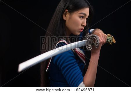 Pretty brunette lady with red lips looking like warrior. Asian lady posing sword for photographer in studio.