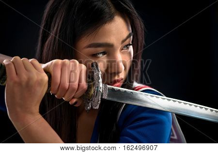 Portrait of pretty brunette lady with red lips looking like warrior. Asian lady posing sword for photographer in studio.