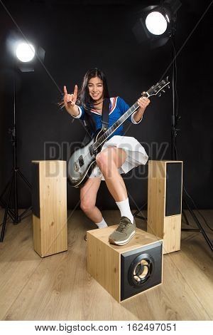 Brunette lady making hard rock music on guitar isolated on black background. Asian rock star lady posing with guitar in studio.
