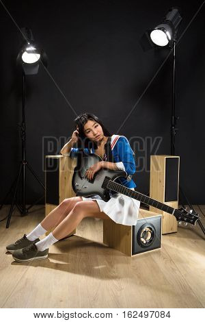 Beautiful Asian rock star lady sitting and holding guitar in studio. Pretty brunette lady resting after hard rock music.
