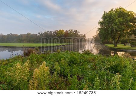 Two fishermen in a boat slide through water of a pond in early morning mist at dawn during sunrise