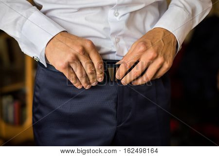 man corrects belt fees groom man's hands dressing man wear pants jeans man's style wedding preparations