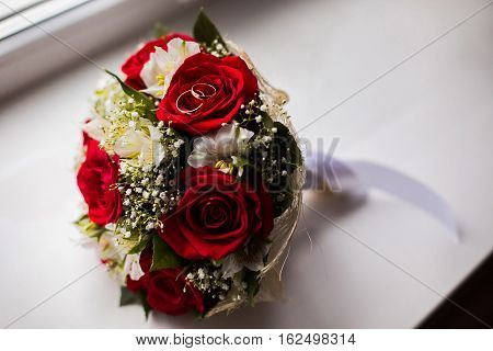 infinity sign of the rings wedding rings on a white backgroundwedding bands wedding rings lie on a bouquet of white flowers and red roses bouquet of roses