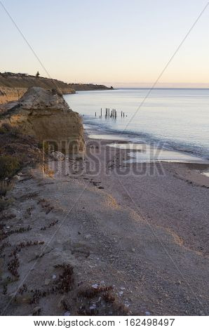 Looking down at the jetty ruins at Port Willunga South Australia during the golden hour nearing sunset and at high tide.