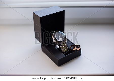 wedding rings on a box of watches wrist watches pocket watches time infinity sign of the rings wedding rings on a black and white backgroundwedding bands Preparations for the wedding the groom's fees