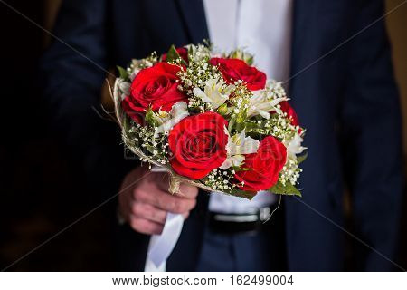 wedding flowers groom holds bouquet of white flowers and red roses bouquet of roses bridal bouquet groom's fees