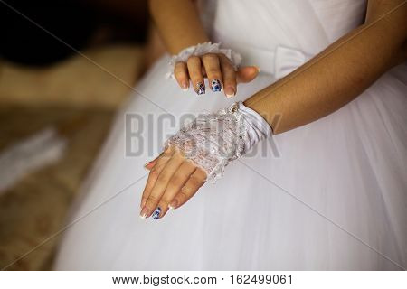 Girl wears wedding gloves on a hand of the bride bride's morning preparing for the wedding the bride's fees dress decorate the bride wedding attributes