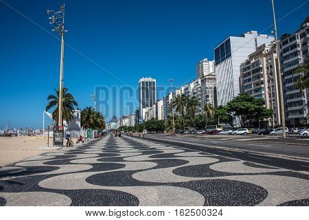 Worldwide famous Copacabana promenade with palm trees residential buildings hotels and black and white mosaic of Portuguese pavement in Rio de Janeiro Brazil