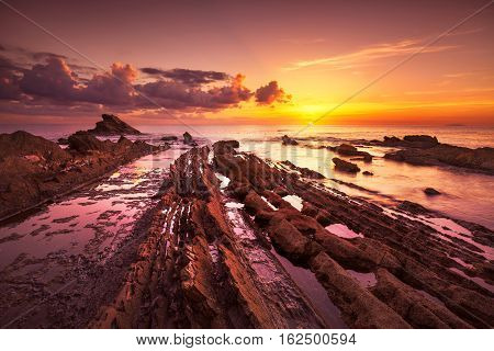 Rocks in a sea on sunset. Tuscany coast Italy Europe