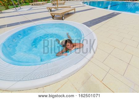 Joyful happy beautiful little girl swimming and relaxing in small Jacuzzi near the pool