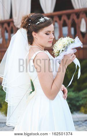 beautiful bride in a white lush dress walks outdoors