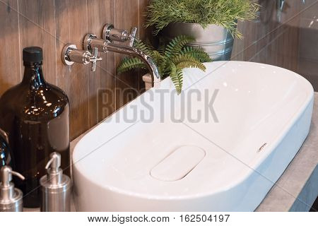 Bathroom sink and faucet, a wooden background.
