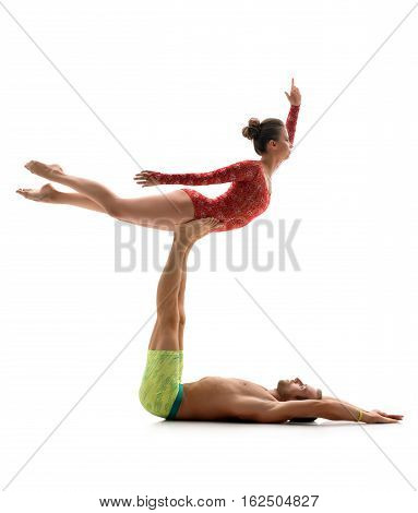 Couple of strong athletic acrobats performing difficult trick together, isolated on white, studio shot