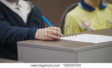 Classmates on school during the lesson - children siting on table and holding pens, close-up telephoto shot