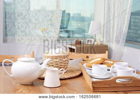 Tray with tea and pastry and Easter basket on the table