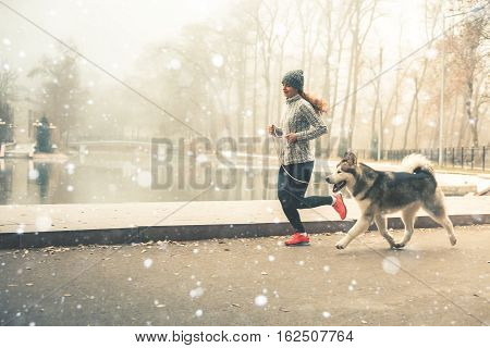 Image of young girl running with her dog, alaskan malamute, outdoor at autumn or winter. Mourning jogging. Domestic pet. Husky. Guide-dog