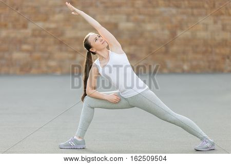 Sporty attractive young woman practicing yoga, standing in Extended Side Angle exercise, Utthita parsvakonasana pose, working out, wearing sportswear, outdoor full length, brick wall background