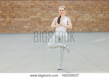 Sporty attractive young woman practicing yoga, standing in Tree exercise, Vriksasana pose, working out, wearing sportswear, outdoor full length, brick wall background