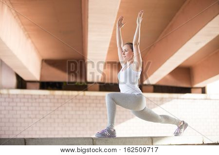 Sporty attractive young girl practicing yoga, standing in Warrior one exercise, Virabhadrasana pose, working out, wearing sportswear, outdoor full length, urban background