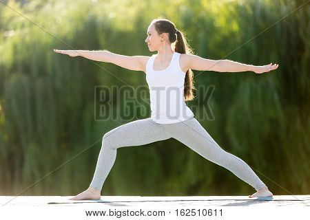 Sporty attractive young woman practicing yoga, standing in Warrior two exercise, Virabhadrasana 2 pose, working out, wearing sportswear, outdoor full length, street background