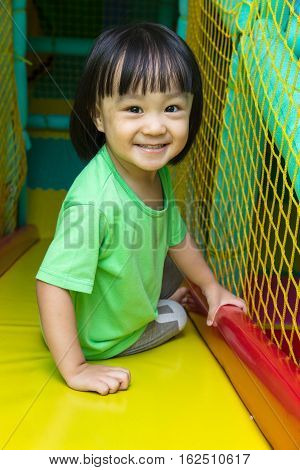 Happy Asian Chinese Little Girl Playing Slide At Indoor Playground