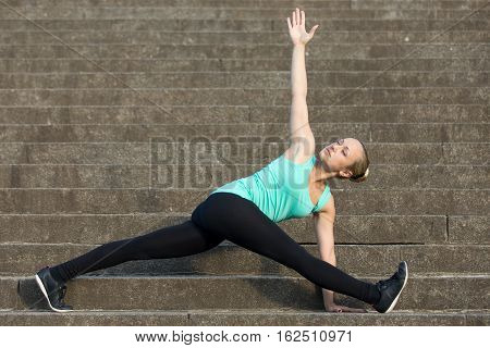 Sporty attractive young woman practicing yoga, sitting in Wide legged revolved Triangle exercise, Parivrrta Trikonasana pose, working out, wearing sportswear, outdoor, urban stone stair background