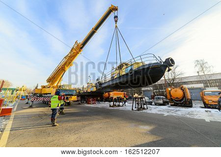 MOSCOW, RUSSIA - NOVEMBER 11, 2016: State Unitary Enterprise Mosvodostok performs recovery vessels on coastal winter parking. Truck crane lowers the ship to the shore.