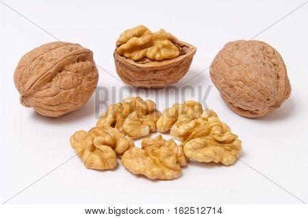 Whole walnuts and walnut kernels on white background