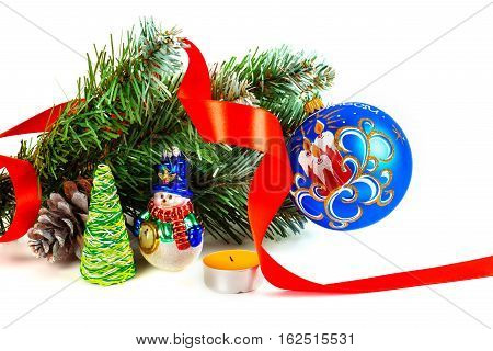 Toy snowman under a branch of an artificial Christmas tree with the cone and a red tape.