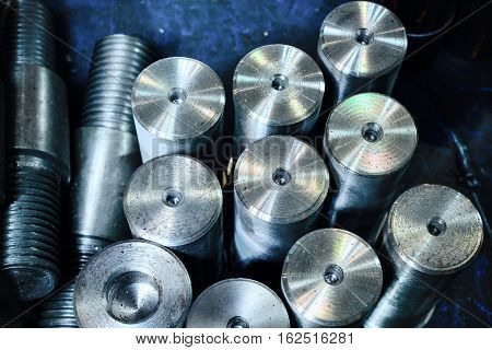 Steel threaded studs. Details made lathe. Shallow depth of field. Abstract industrial background.