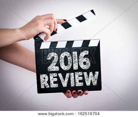 2016 Review concept. Female hands holding movie clapper.