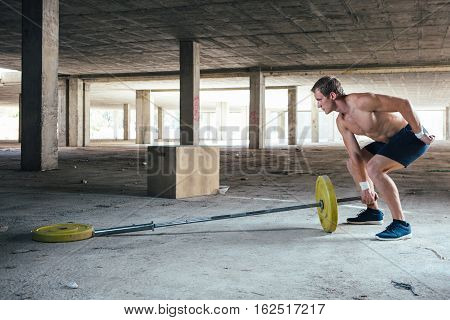 Side view of strong man lifting weight on crossbar. Horizontal indoor shot