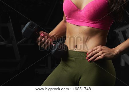 Sporty woman with piercing in belly button close up