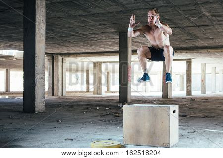 Front view of man with naked torso doing box jumps. Horizontal indoor shot