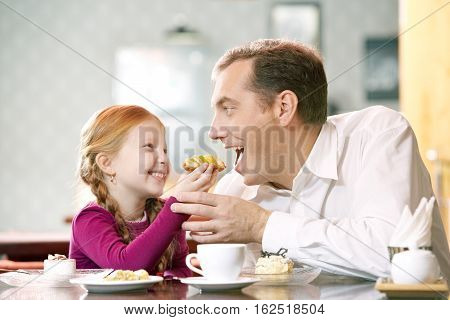 Little girl treating his father with a pastry at cafe