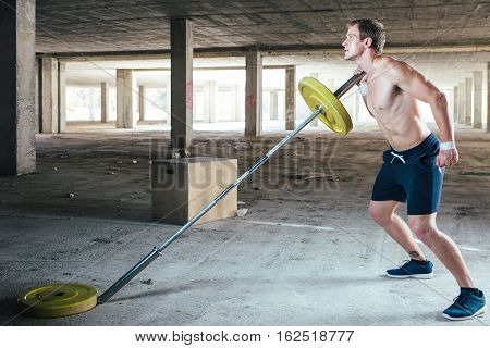 Side view of muscular man lifting weight on crossbar in abandoned building.