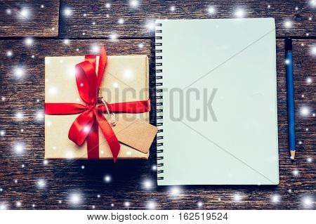 Brown Gift Box And Notebook, Pencil With Snow White On Wood Board Background With Space.