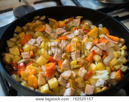 Picture of the frying colourful meal in the frying pan close up. Background like pattern. Black frying pan on a white gas stove.